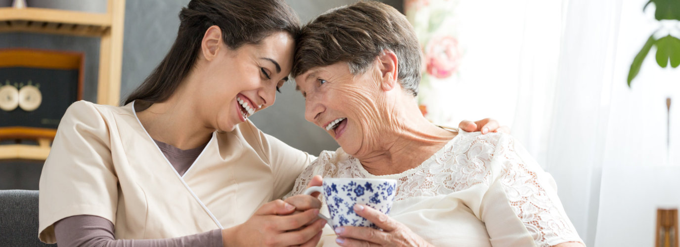 caregiver and senior woman smiling at each other